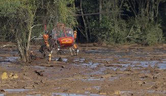 Rescue workers in a helicopter look for victims of a dam collapse in Brumadinho, Brazil, Sunday, Jan. 27, 2019. A massive, deadly river of pale brown mud released by the collapse of a mining company dam on Friday threatens to cause an environmental disaster for Brazil, potentially snatching away livelihoods and driving the spread of disease, activists warned Sunday. (AP Photo/Andre Penner)