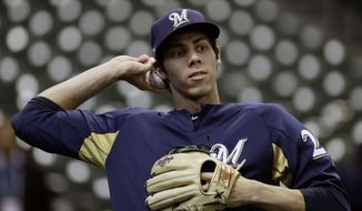 FILE - In this Oct. 12, 2018, file photo, Milwaukee Brewers' Christian Yelich warms up before Game 1 of the National League Championship Series baseball game against the Los Angeles Dodgers in Milwaukee. After falling one game short of their first World Series appearance since 1982, there is plenty of pressure on the Brewers to build on that success and take another step forward in 2019. Nobody on the roster is likely to feel that pressure more than Yelich, whose record-breaking performance down the stretch fueled Milwaukee's postseason run and earned the National League's Most Valuable Player award. (AP Photo/Matt Slocum, File)