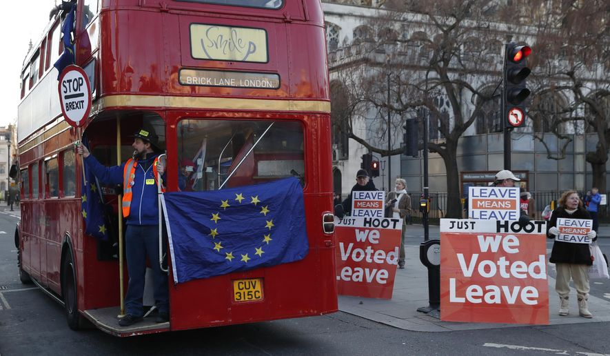 Anti Brexit protesters on board a hired red London bus demonstrate as they drive past the Houses of Parliament in London, Monday, Jan. 28, 2019. Pro-Brexit British lawmakers were mounting a campaign Monday to rescue May's rejected European Union divorce deal in a parliamentary showdown this week. (AP Photo/Alastair Grant)