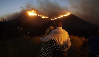 FILE - In this Nov. 9, 2018 file photo, Roger Bloxberg, right, and his wife, Anne, embrace as they watch a wildfire on a hill top near their home in West Hills, Calif. Insurance claims from California's deadly November 2018 wildfires have topped $11.4 billion. State Insurance Commissioner Ricardo Lara said Monday, Jan. 28, 2019, that more than $8 billion worth of damage comes from the fire that leveled the town of Paradise and killed 86 people. About $3 billion more is from two Southern California wildfires that ignited the same week. (AP Photo/Marcio Jose Sanchez, File)