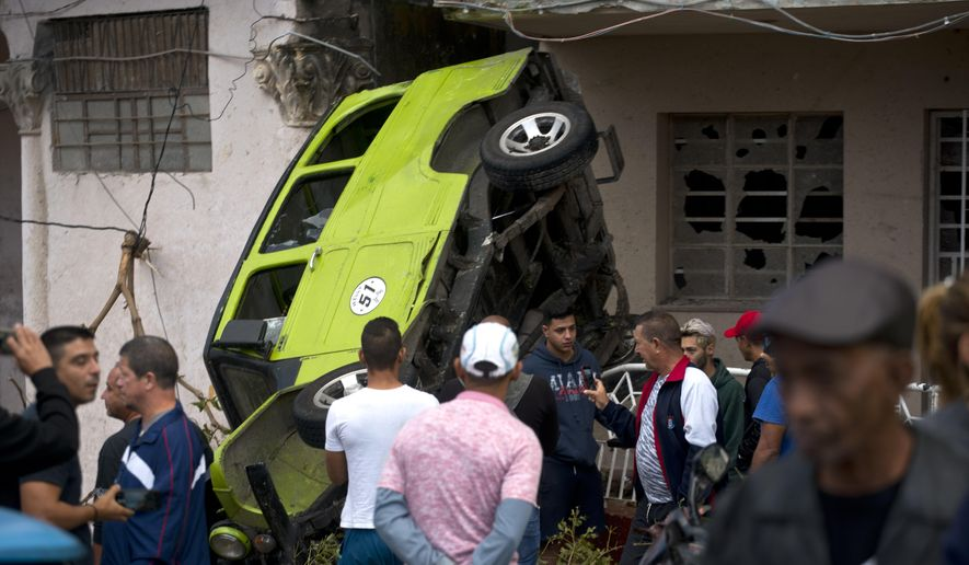 People stand around a car that was overturned by a tornado in Havana, Cuba, Monday, Jan. 28, 2019. A tornado and pounding rains smashed into the eastern part of Cuba's capital overnight, toppling trees, bending power poles and flinging shards of metal roofing through the air as the storm cut a path of destruction across eastern Habana. (AP Photo/Ramon Espinosa)