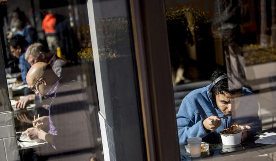 Workers eat lunch at a restaurant along K Street in downtown Washington, Monday, Jan. 28, 2019.  The shutdown started in December over funding for President Donald Trump's promised U.S.-Mexico border wall. Trump on Friday agreed to end the shutdown for three weeks. (AP Photo/Andrew Harnik)