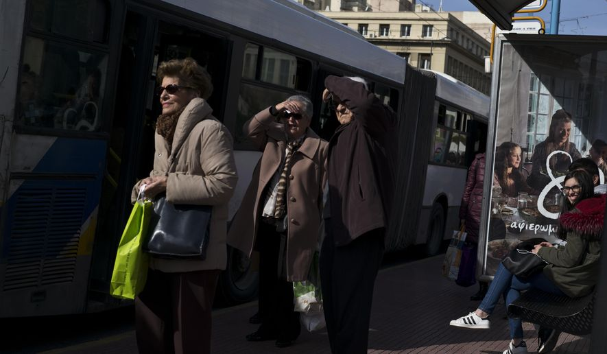 People wait at a bus station in central Athens, on Monday, Jan. 28, 2019. Greece announced plans to issue a 5-year bond, in the first market test since the end of its international Bailout last August. (AP Photo/Petros Giannakouris)