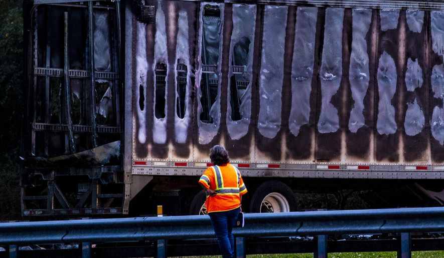 FILE - In this Thursday, Jan. 3, 2019, file photo, a worker looks at a charred semitrailer after a wreck with multiple fatalities on Interstate 75, south of Alachua, near Gainesville, Fla. The 35-day partial government shutdown stopped the National Transportation Safety Board from dispatching investigators to 22 accidents that killed 30 people, jeopardizing some perishable evidence, the agency said Monday, Jan. 28, 2019. (Lauren Bacho/The Gainesville Sun via AP, File)
