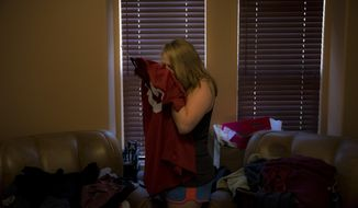"""Brittaney Biggers, whose 20-year-old brother, Landon, died of opioid overdose in 2017, smells a football jersey her brother used to wear in La Quinta, Calif., on Tuesday, Aug. 14, 2018. """"It still smells like him,"""" she says. She had moved in with her parents to save money for her own apartment and planned to stay a couple months. Then her brother died, and she picked up a second job at a bar so she could work six days a week and be so tired on the seventh she wouldn't have to face it. (AP Photo/Jae C. Hong)"""
