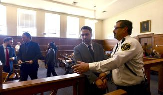 Mark Fitzgerald, of Ashland, Mass., is led by a district court officer, Monday, Jan. 28, 2019, in Waltham, Mass., where he was arraigned on charges including assault with a dangerous weapon. Two Massachusetts men involved in an apparent case of road rage in which one drove at speeds of up to 70 mph with the other clinging to the hood of his car, have been arraigned. (Faith Ninivaggi/MediaNews Group/Boston Herald via AP, Pool)