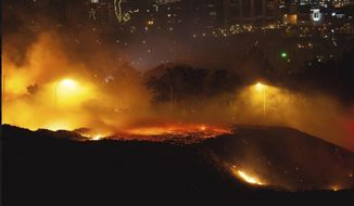 This image provided by Justin Engel shows a fire in Cape Town, South Africa, Sunday Jan. 27, 2019. Cape Town officials say they have controlled a fire that blazed overnight around the city's iconic Lion's Head hill, injuring one man. The Cape Town area remains on high alert because of hot, dry conditions and windy weather. (Justin Engel via AP)