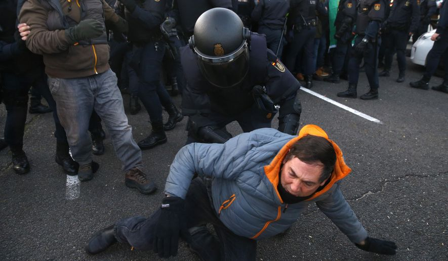 Police officers remove taxi drivers who were blocking the Castellana avenue, during a strike in Madrid, Spain, Monday, Jan. 28, 2019. Police are clearing taxis blocking a main avenue in the Spanish capital as part of a weeklong standoff with authorities over the growth of app-based ride-hailing services that they say threaten their livelihood. The striking taxi drivers want the regional government in Madrid to impose tighter regulations for rides hailed through apps like Uber and Cabify. (AP Photo/Andrea Comas)