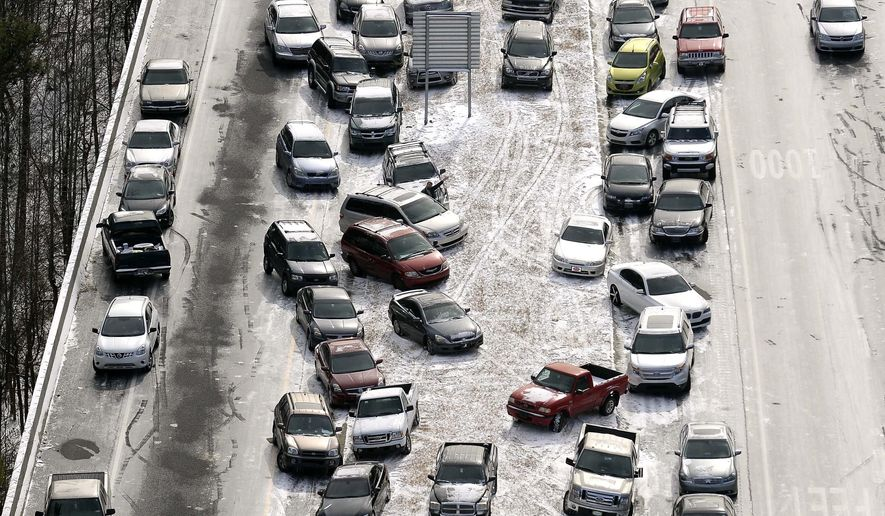 FILE-In this Jan. 29, 2014 aerial file photo, abandoned cars at I-75 headed northbound near the Chattahoochee River overpass are piled up in the median of the ice-covered interstate after a winter snow storm, in Atlanta. A winter storm watch goes into effect at 4 a.m. Tuesday, Jan. 29, for Atlanta, a city known for its ability to grind to a halt even in relatively light snowfalls. (AP Photo/David Tulis, File)