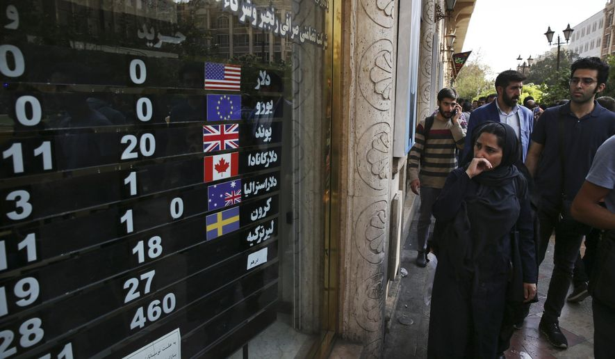 FILE - In this Oct. 2, 2018, file photo, an exchange shop displays rates for various currencies, in downtown Tehran, Iran. The Trump administration is closely eyeing efforts in Europe to set up an alternative money payment channel to ease doing business with Iran and avoid running afoul of sanctions the U.S. has levied on the Islamic republic. (AP Photo/Vahid Salemi, File)