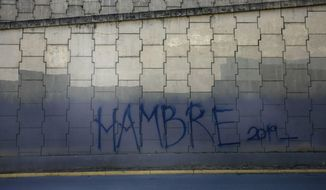 """Graffiti that reads in Spanish: """"Hunger 2019"""" covers a highway wall in Caracas, Venezuela, Sunday, Jan. 27, 2019. Venezuelans are struggling with hyperinflation and widespread food shortages. (AP Photo/Rodrigo Abd)"""