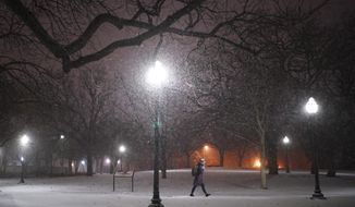 A woman walks across the snowy University of Minnesota campus near Dinkytown neighborhood in Minneapolis on Sunday, Jan. 27, 2019. A winter storm pushing across the Upper Midwest is expected to dump more than a foot of snow in parts of Minnesota and Wisconsin. (Jeff Wheeler/Star Tribune via AP)