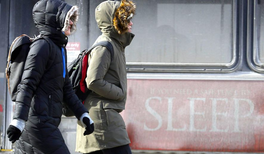 People are bundled up against record cold in Chicago, even as a hot debate on the role of climate change continues in the news media. (Asspcoated Press)