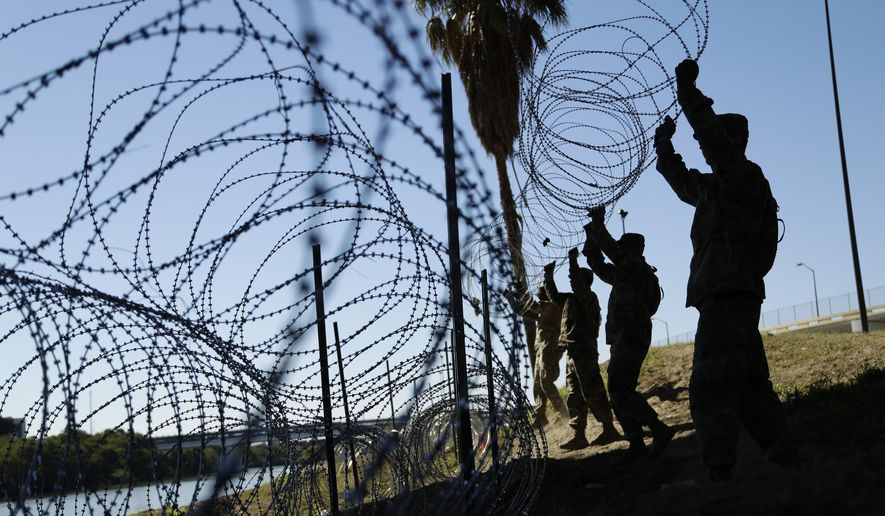 In this Nov. 16, 2018, file photo, members of the U.S. military install multiple tiers of concertina wire along the banks of the Rio Grande near the Juarez-Lincoln Bridge at the U.S.-Mexico border in Laredo, Texas. On Feb. 6, 2019, the Pentagon confirmed it has moved some troops to Eagle Pass, Texas, to counter the threat posed by a new migrant caravan that's arrived on the U.S.-Mexico border. (AP Photo/Eric Gay, File) **FILE**