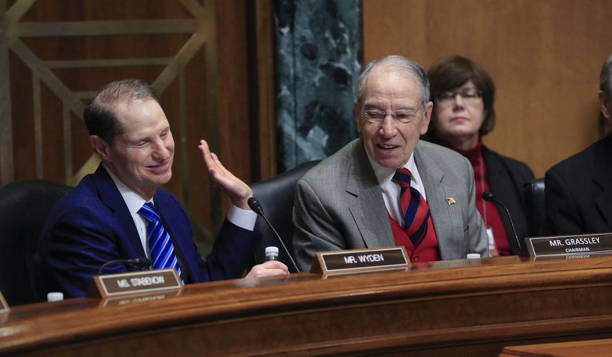 Sen. Chuck Grassley, R-Iowa, right, chairman of the Senate Finance Committee, smiles as he is joined at left by Sen. Ron Wyden, D-Ore., the ranking member, during a bipartisan start to a hearing on the high price of prescription drugs, on Capitol Hill in Washington, Tuesday, Jan. 29, 2019. (AP Photo/J. Scott Applewhite) **FILE*