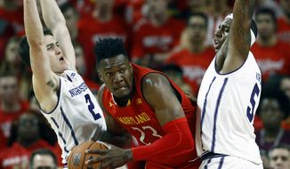 Maryland forward Bruno Fernando, center, of Angola, drives between Northwestern guard Ryan Greer, left, and center Dererk Pardon in the first half of an NCAA college basketball game, Tuesday, Jan. 29, 2019, in College Park, Md. (AP Photo/Patrick Semansky)