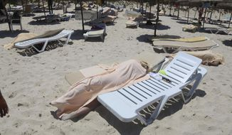 FILE - In this Friday, June 26, 2015 file photo, covered bodies lie on a beach in Sousse, Tunisia. More than 30 people have been summoned to face trial over the Tunisia's deadliest attack in a Mediterranean resort. The trial is scheduled to reopen on Tuesday Jan.29, 2019 in Tunis, more than 3-1/2 years after the attack on the Imperial Hotel in the beach resort of Sousse left 38 people dead, mostly British tourists. (Jawhara FM via AP, File)