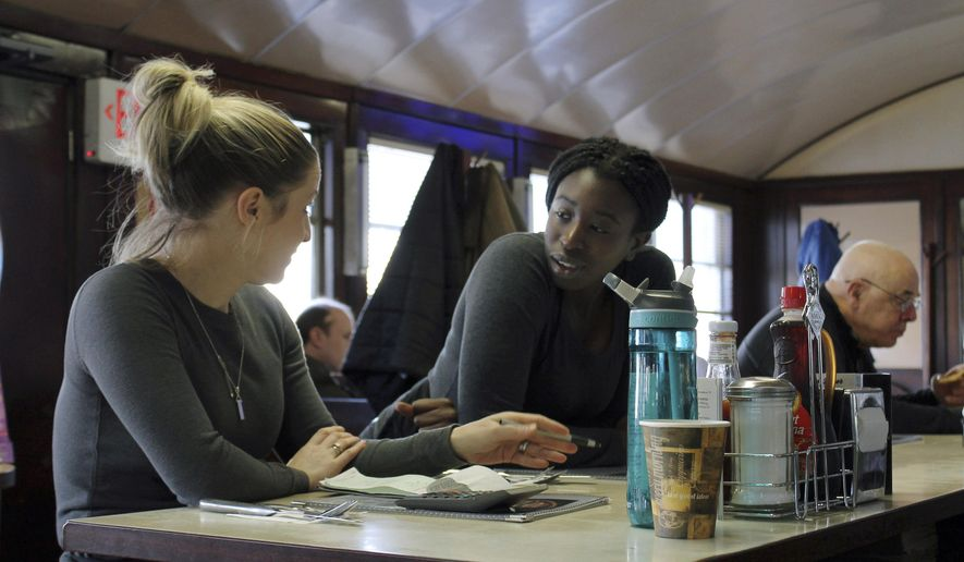 In this Friday, Jan. 25, 2019, waitress Kelcie Tipping, left, speaks with fellow waitress Mariam Touray, right, at the Modern Diner in Pawtucket, R.I. A large majority of Americans say they are pessimistic about the state of the country and few expect things will get better in the year ahead, according to a poll released Tuesday by The Associated Press-NORC Center for Public Affairs Research.  (AP Photo/Michelle R. Smith)