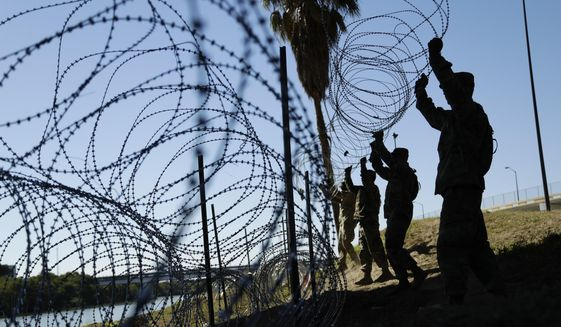 In this file photo, members of the U.S. military install multiple tiers of concertina wire along the banks of the Rio Grande near the Juarez-Lincoln Bridge at the U.S.-Mexico border in Laredo, Texas. (AP Photo/Eric Gay, File)  **FILE**