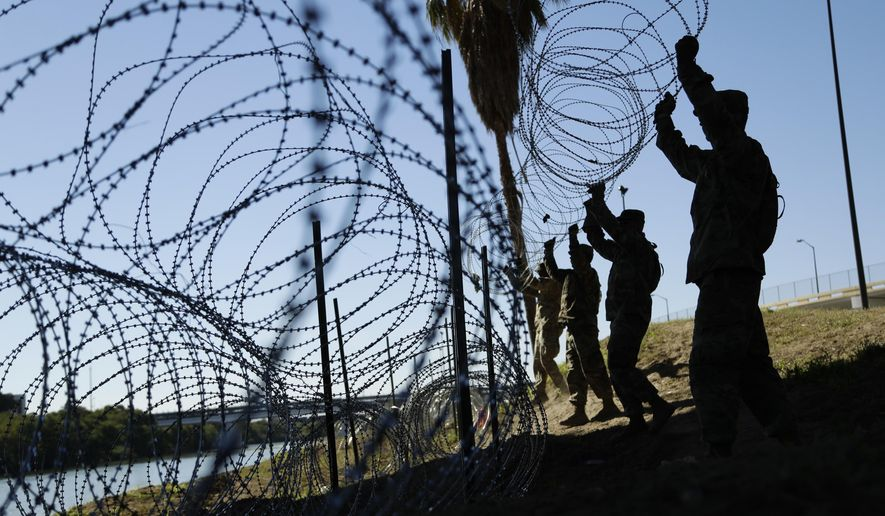 Members of the U.S. military install multiple tiers of concertina wire along the banks of the Rio Grande near the Juarez-Lincoln Bridge at the U.S.-Mexico border in Laredo, Texas. (AP Photo/Eric Gay, File)