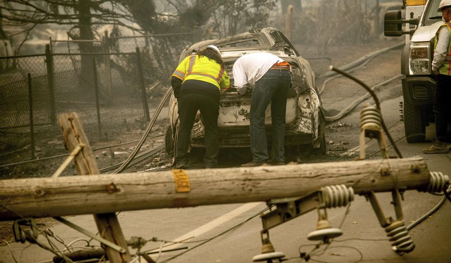 In this Nov. 10, 2018, file photo, with a downed power utility pole in the foreground, Eric England, right, searches through a friend's vehicle after the wildfire burned through Paradise, Calif. Pacific Gas & Electric Corp. is expected to file for bankruptcy protection Tuesday, Jan. 29, 2019. (AP Photo/Noah Berger, File)