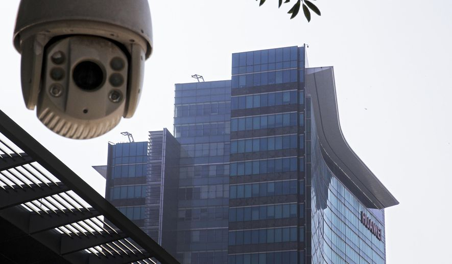 In this Dec. 18, 2018, file photo, a surveillance camera is mounted near the Huawei headquarters in Shenzhen in south China's Guangdong province. (AP Photo/Andy Wong) ** FILE **