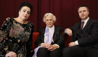 Holocaust survivor Anita Lasker-Wallfisch, center, her daughter Maya Jacobs Lasker-Wallfisch, left, and her grandson Simon Wallfisch, right, the son of Maya Jacobs Lasker-Wallfisch, pose for a photo after an interview with the Associated Press in Berlin, Germany, Sunday, Jan. 27, 2019. Maya Jacobs Lasker-Wallfisch and Simon Wallfisch, are two of thousands of Jews in Britain have applied for restoration of German citizenship stripped from their ancestors by the Nazis during the Third Reich. (AP Photo/Markus Schreiber)