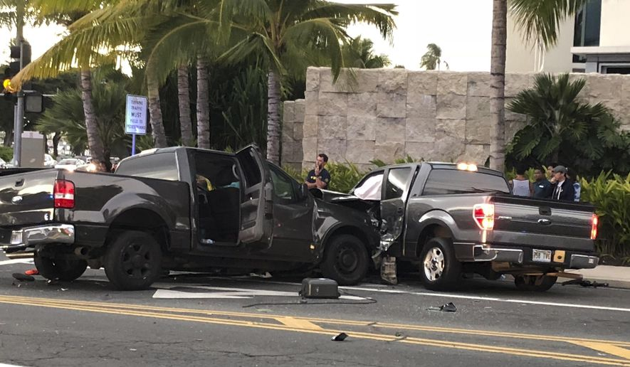 In this photo taken Monday, Jan. 28, 2019, is the scene of a multiple vehicle accident involving two trucks and a bicyclist in Honolulu. Police say a suspected drunk driver in a pickup truck slammed into a crowded Honolulu intersection, killing two pedestrians and a bicyclist and injuring five people including himself. Alcohol and speed may have played a role in the crash shortly before 6:30 p.m. Monday in the Kakaako neighborhood, according to authorities. (Cindy Ellen Russell/Honolulu Star-Advertiser via AP)