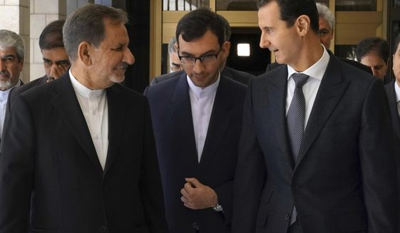 "In this photo released by the Syrian official news agency SANA, Syrian President Bashar Assad, right, speaks with Iran's first Vice President Eshaq Jahangiri, left, in Damascus, Syria, Tuesday, Jan. 29, 2019. Syria's president said Tuesday that new trade agreements with Iran will help the two countries face the ""economic war"" waged against them by the West. Syria's government is under heavy Western sanctions linked to its actions over the course of the civil war. Iran, a close ally of Assad, is under renewed U.S. sanctions following President Donald Trump's decision to withdraw from the 2015 nuclear deal. (SANA via AP)"