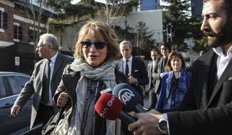 United Nations Special Rapporteur Agnes Callamard, surrounded by members of the media walks around the Saudi Consulate, background, in Istanbul, Tuesday, Jan. 29, 2019. Callamard and her team of experts on extrajudicial, summary or arbitrary killings is in Turkey for a weeklong visit over the killing of Saudi journalist Jamal Khashoggi. Khashoggi, a Washington Post columnist who wrote critically about the Saudi crown prince, was killed inside the Saudi Consulate in Istanbul on Oct. 2, 2018. (Cemal Yurttas/DHA via AP)