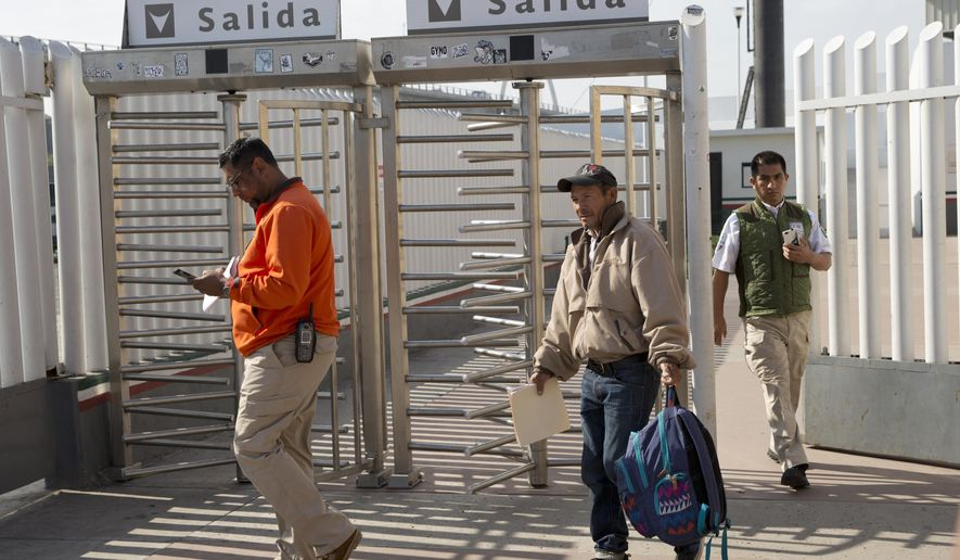 Carlos Catarldo Gomez, of Honduras, center, is escorted by Mexican officials after leaving the United States, the first person returned to Mexico to wait for his asylum trial date, in Tijuana, Mexico, Tuesday, Jan. 29, 2019. The Trump administration has launched an effort to make asylum seekers wait in Mexico while their cases wind through U.S. immigration courts despite mixed signals from Mexico on key issues. (AP Photo/Gregory Bull)