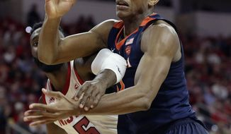 Virginia's De'Andre Hunter and North Carolina State's Eric Lockett (5) reach for the ball during the second half of an NCAA college basketball game in Raleigh, N.C., Tuesday, Jan. 29, 2019. Virginia won 66-65 in overtime. (AP Photo/Gerry Broome)