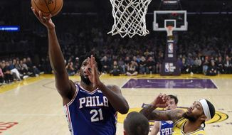 Philadelphia 76ers center Joel Embiid, left, shoots as Los Angeles Lakers forward Brandon Ingram, right, defends during the first half of an NBA basketball game Tuesday, Jan. 29, 2019, in Los Angeles. (AP Photo/Mark J. Terrill)