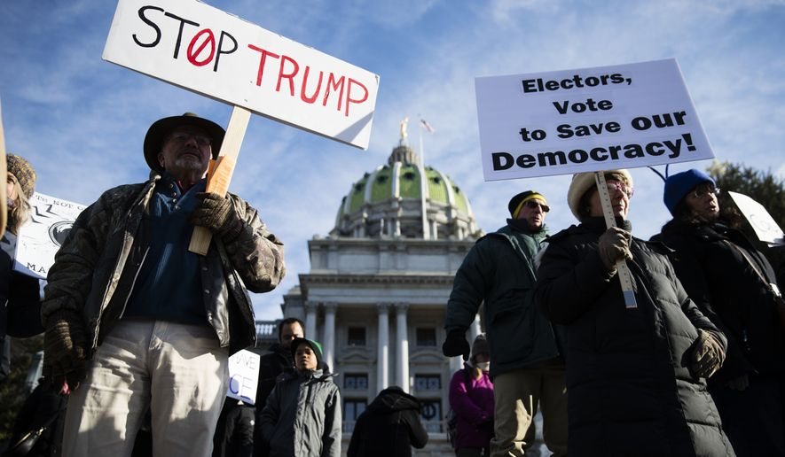 Protesters demonstrate ahead of Pennsylvania's 58th Electoral College at the state Capitol in Harrisburg, Pa., Monday, Dec. 19, 2016. The demonstrators were waving signs and chanting in freezing temperatures Monday morning as delegates began arriving at the state Capitol to cast the state's electoral votes for president. (AP Photo/Matt Rourke) **FILE**