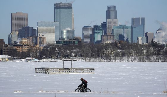 A cyclist decked out in cold weather gear rides past the city skyline and a frozen Bde Maka Ska in Minneapolis.(Anthony Souffle/Star Tribune via AP)  ** FILE **