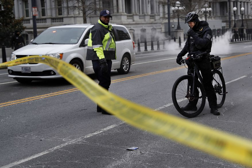 With steam from an underground grate in the background, a Metropolitan Police officer and Secret Service Police officer react to a large gust of frigid wind while blocking the road on 17th Street at the intersection with Pennsylvania Avenue near the White House in Washington, Wednesday, Jan. 30, 2019. (AP Photo/Jacquelyn Martin)