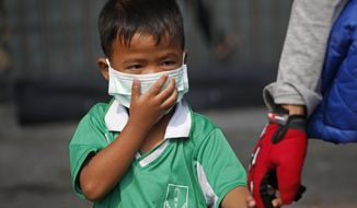 A young boy wears a protective mask for the high levels of air pollution as he's picked up from school in Bangkok, Thailand, Wednesday, Jan. 30, 2019. Over 400 schools in Bangkok have been ordered shut Wednesday as the Thai capital sees continuously high levels of air pollution and dust particles. (AP Photo/Sakchai Lalit)