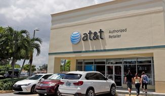FILE- In this July 27, 2017, file photo shows an AT&T store in Hialeah, Fla. AT&T Inc. reports earnings Wednesday, Jan. 30, 2019. (AP Photo/Alan Diaz, File)