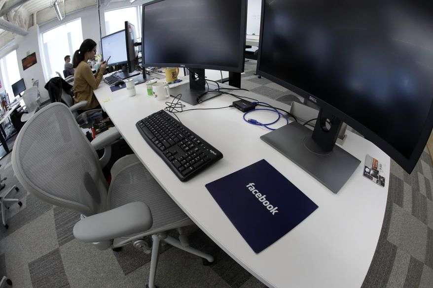 In this Jan. 9, 2019, file photo, Facebook employees sit at their stations during a tour of its new 130,000-square-foot offices, which occupy the top three floors of a 10-story Cambridge, Mass., building. Facebook reports earnings Wednesday, Jan. 30, 2019. (AP Photo/Elise Amendola, File)