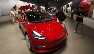 FILE- In this July 6, 2018, file photo prospective customers confer with sales associates as a Model 3 sits on display in a Tesla showroom in the Cherry Creek Mall in Denver. Tesla reports earnings Wednesday, Jan. 30, 2019. (AP Photo/David Zalubowski, File)