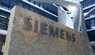 FILE - This June 24, 2016 file photo, showing the logo of German industrial conglomerate Siemens at their headquarters in Munich, Germany.  Siemens AG, maker of power generation and transmission equipment, as well as trains and medical imaging devices, reports on Wednesday Jan. 30, 2019, its earnings for the most recent quarter.  (AP Photo/Matthias Schrader, FILE)