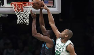 Boston Celtics center Al Horford (42) blocks a shot by Charlotte Hornets center Bismack Biyombo, left, during the first quarter of an NBA basketball game in Boston, Wednesday, Jan. 30, 2019. (AP Photo/Charles Krupa)