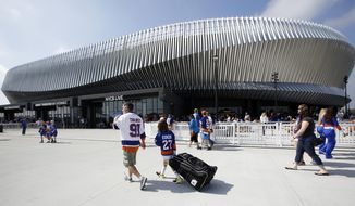 FILE - In this Sept. 17, 2017 file photo, hockey fans make their way toward the entrances of the renovated Nassau Veterans Memorial Coliseum in Uniondale, N.Y., before a preseason NHL hockey game between the New York Islanders and the Philadelphia Flyers. This season is the first of three in which the Islanders will play half its home schedule at the sleek Barclays Center in Brooklyn and the rest in the venerable Nassau Coliseum on Long Island. So far, the fans have made it clear they prefer the old barn. The win-loss record says the team prefers that, too.  (AP Photo/Kathy Willens, File)
