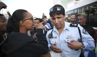 A woman argues with a policeman as members of Israeli-Ethiopian community protest against police and demand the appointment of an investigating judge to probe the killing of Yehuda Biadga, a mentally ill Ethiopian-Israeli, by Israeli police, in Tel Aviv, Israel, Wednesday, Jan. 30, 2019. (AP Photo/Oded Balilty)