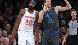 Dallas Mavericks forward Dirk Nowitzki (41) signals to his bench with New York Knicks center Mitchell Robinson (26) awaiting the an official's call during the first half of an NBA basketball game, Wednesday, Jan. 30, 2019, in New York. (AP Photo/Kathy Willens)