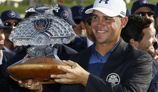 FILE- In this Feb. 4, 2018, file photo, Gary Woodland smiles for photographers with the championship trophy after winning the Waste Management Phoenix Open golf tournament in Scottsdale, Ariz. Woodland won the 2018 Phoenix Open for his first victory in five years. He returns to the desert this weekend, hoping to defend his title at the Greatest Show on Turf. (AP Photo/Ross D. Franklin, File)
