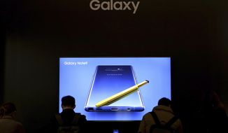 In this Wednesday, Jan. 30, 2019, photo, visitors try out Samsung Electronics' Galaxy Note9 smartphones during an industrial fair in Seoul, South Korea. South Korean technology giant Samsung posted on Thursday, Jan. 31, 2019, a near-30 percent drop in operating profit for the last quarter after seeing slowing global demand for its memory chips and smartphones. (AP Photo/Ahn Young-joon)