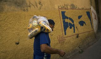 With a mural depicting the eyes of Veneuzela's late President Hugo Chavez, Carlos Gonzales carries a bag with food delivered by the government for the poorest people in the Antimano neighborhood of Caracas, Venezuela, Tuesday, Jan. 29, 2019. Venezuela's President Nicolas Maduro went on state television Tuesday to announce that he was beefing up the nation's defense by expanding Venezuela's civilian armed militia to 2 million members. The reserve force was created by the late Hugo Chavez to train civilians to assist the armed forces and defend the socialist revolution from attacks. (AP Photo/Rodrigo Abd)
