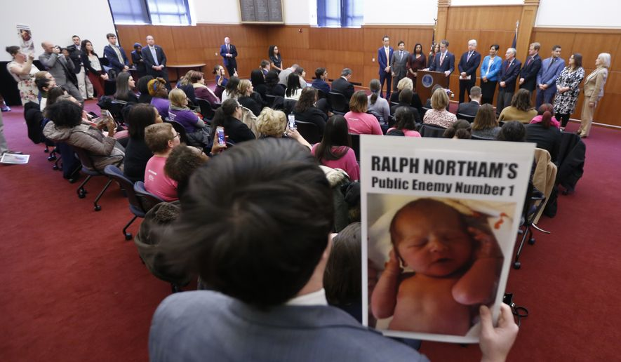 A demonstrator holds a sign as Gov. Ralph Northam, at podium, gives a news conference at the Capitol in Richmond, Va., Thursday, Jan. 31, 2019. Northam made a statement and answered questions about the late term abortion bill that was killed in committee. (AP Photo/Steve Helber) **FILE**