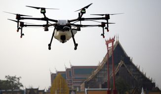 A drone is flown over the Suthat Temple in Bangkok, Thailand, Thursday, Jan. 31, 2019. Bangkok's municipal government displayed six drones that will be used to spray water over the city to help ease high levels of pollution. More than 400 schools in Thailand's capital were shut for the rest of the week Wednesday due to increasing concern over dangerously unhealthy air pollution. (AP Photo/Sakchai Lalit)